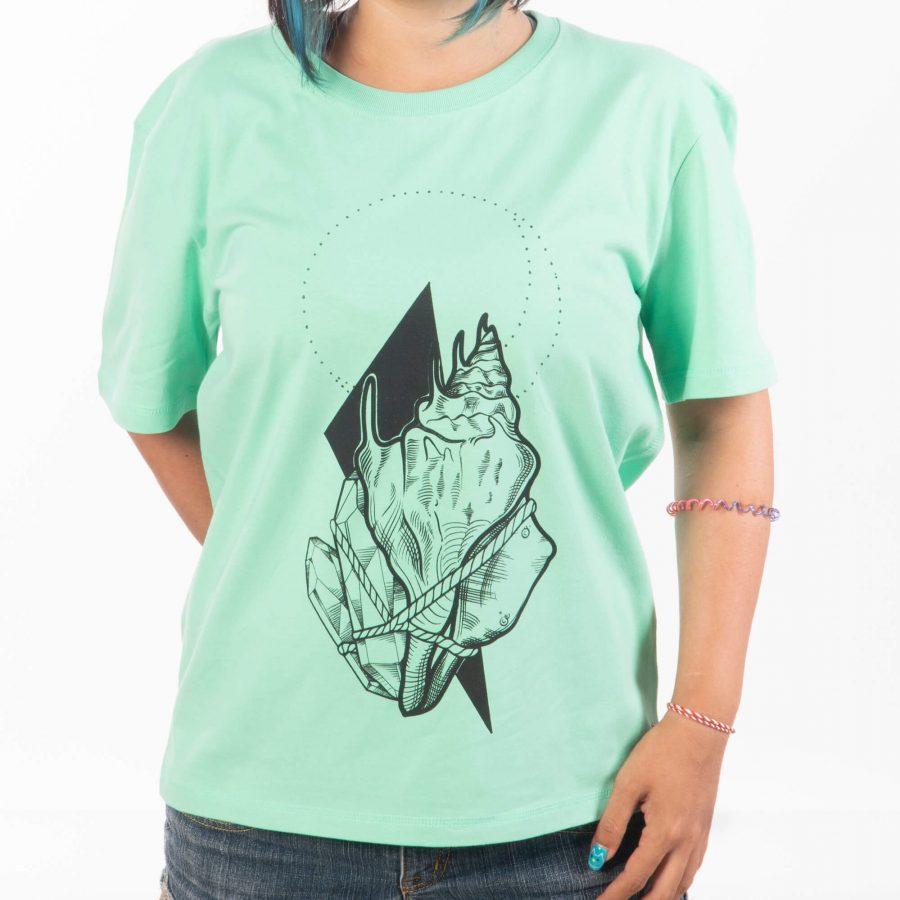 млада жена с ръка зад гърба в широка ментова тениска от фин органичен памук с художествен отпечатък