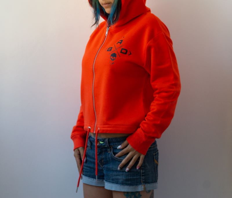 жена заснета в профил облечена в суичър в наситено оранжево