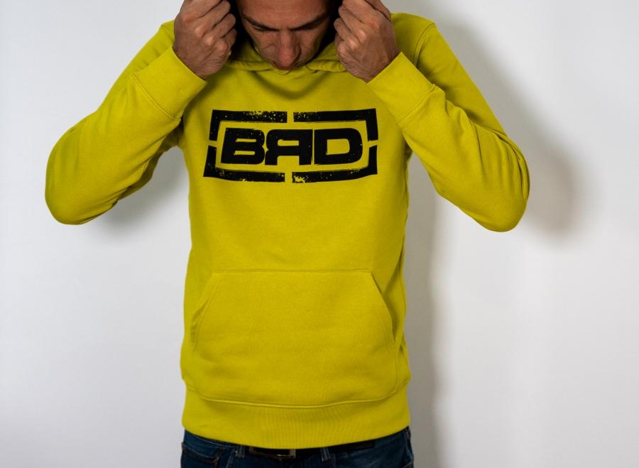 мъж с плътно жълто горнище с качулка